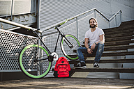 Smiling young man sitting on stairs next to fixie bike - RAEF001124