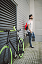 Fixie bike and young man leaning against wall - RAEF001130