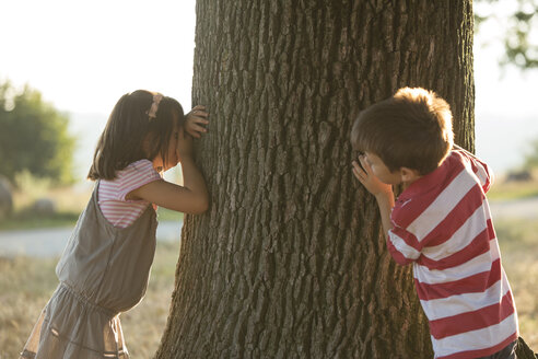 Little boy and girl playing hide and seek in nature - ZOCF000120