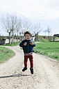 Portrait of happy little boy jumping in the air - XCF000084