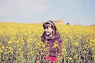 Portrait of little girl standing in front of rape field - XCF000087