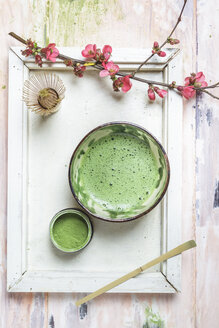 Matcha tea in bowl, with match powder, spoon and chasen and pink flowers - SBDF002859