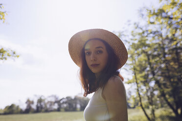 Portrait of young woman wearing straw hat in nature - GIOF000910
