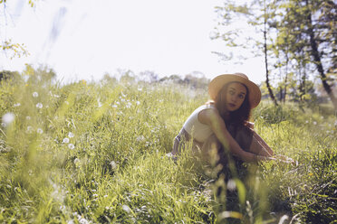 Young woman wearing straw hat sitting on a meadow - GIOF000913