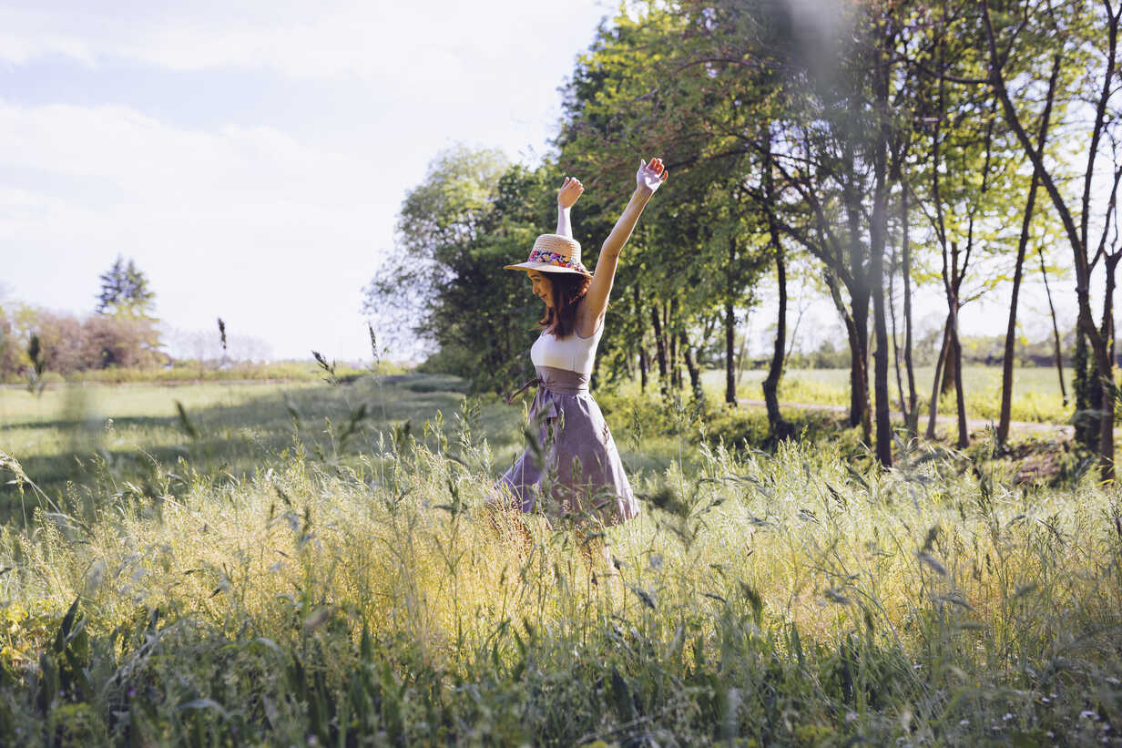 Happy young woman on a meadow in spring - GIOF000919 - Giorgio Fochesato/Westend61