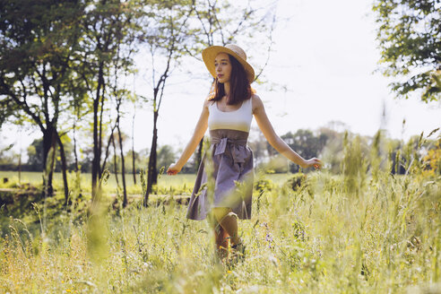 Young woman dancing on a meadow in spring - GIOF000922