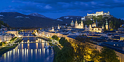 Austria, Salzburg, panoramic view of Salzach river, old town and castle Hohensalzburg at sunset - YRF000102