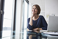 Smiling businesswoman at office desk - RBF004425