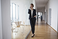 Businesswoman on cell phone in office hall - RBF004443