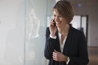 Happy businesswoman on cell phone - RBF004446