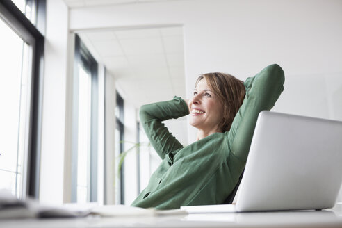Smiling businesswoman at office desk leaning back - RBF004458