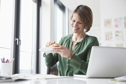 Smiling businesswoman having lunch break at office desk - RBF004461