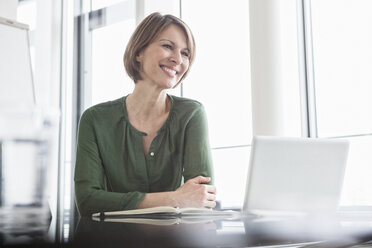 Smiling businesswoman at office desk - RBF004470