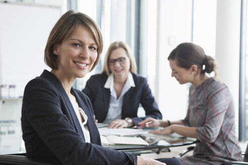 Portrait of smiling businesswoman in a meeting - RBF004491