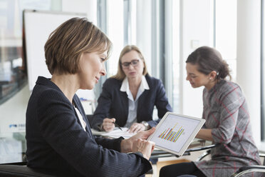 Businesswoman using digital tablet in a meeting - RBF004494