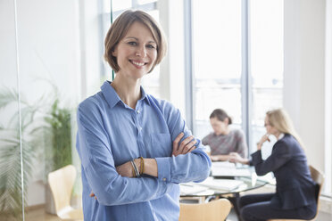 Portrait of smiling businesswoman with colleagues in background - RBF004503
