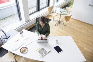 Businesswoman using laptop at office desk - RBF004530