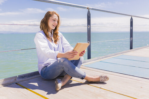 Portrait of young woman using digital tablet in front of the sea - BOYF000298