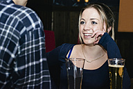 Smiling woman talking with a man in a bar - ABZF000395