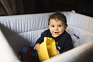 Portrait of smiling baby boy playing in cot - JASF000707
