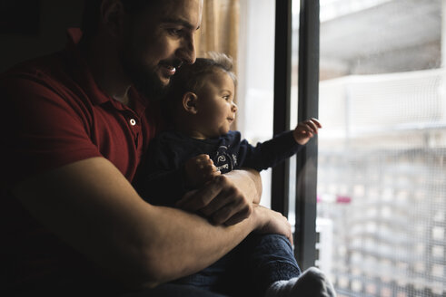Happy father with his baby boy in front of the window - JASF000710