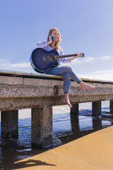 Woman with smartphone and guitar sitting on jetty - BOYF000335