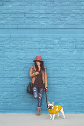 Woman with her French bulldog in front of blue wall - RTBF000169