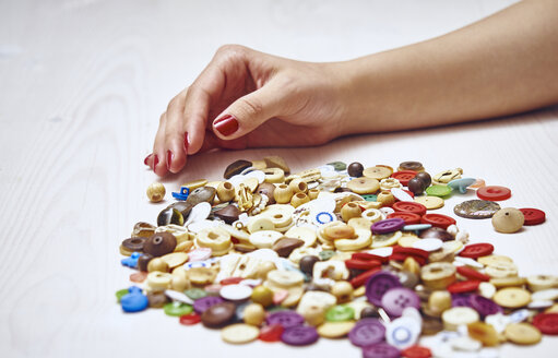 Hand and heap of buttons - DISF002469