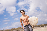 Portrait of young man with surfboard - SIPF000410