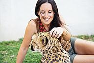 Namibia, Kamanjab, tourist petting a tame cheetah - GEMF000890