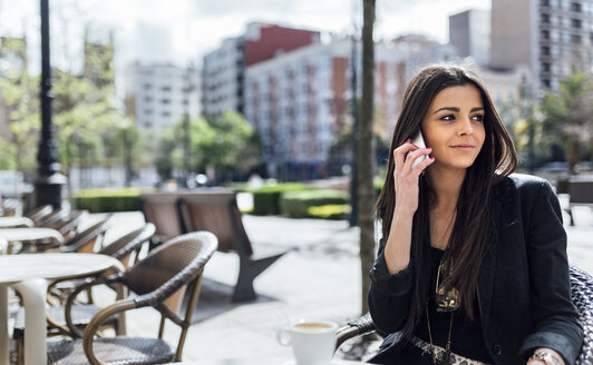 Young woman with smartphone having coffee - MGOF001793