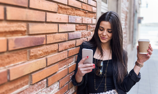 Young beautiful woman drinking a take away coffee and smartphone, leaning on wall - MGOF001808
