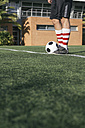 Legs of football player with ball on football ground - ABZF000447
