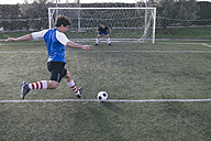 Football player kicking a ball in front of a goal with a goalkeeper - ABZF000453