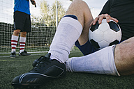 Legs of a man with football clothes sitting on the grass with a ball - ABZF000459