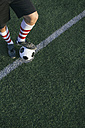 Legs of football player with ball on football ground - ABZF000468