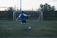 Football player kicking a ball in front of a goal with a goalkeeper - ABZF000474