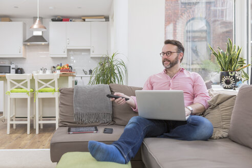 Mature man sitting on couch using laptop and remote control - BOYF000341