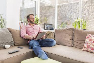 Mature man sitting on couch using digital tablet - BOYF000347