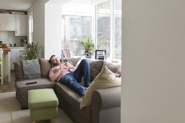 Mature mna lying on couch checking messages on smart phone - BOYF000356