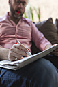 Mature man sitting on couch marking advertisments in newspaper - BOYF000359