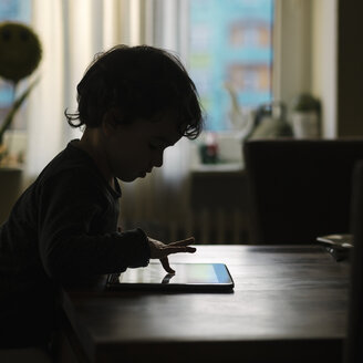 Silhouette of little girl playing with digital tablet at home - KRPF001739