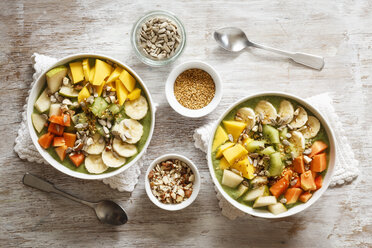 Smoothie bowl with different fruits, mango, papaya, kiwi, banana and pear and toppings, lineseeds, sunflower-seeds and nuts - EVGF002933