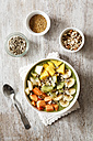 Smoothie bowl with different fruits, mango, papaya, kiwi, banana and pear and toppings, lineseeds, sunflower-seeds and nuts - EVGF002936