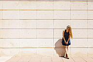 Happy woman leaning against wall in summer - JRFF000597