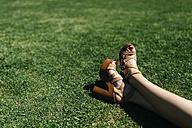 Feet of woman relaxing on lawn - JRFF000600