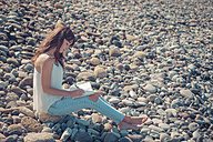 Woman sitting on stony beach writing in her notebook - SIPF000417