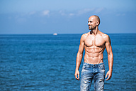 Muscular man standing in front of the sea - SIPF000420