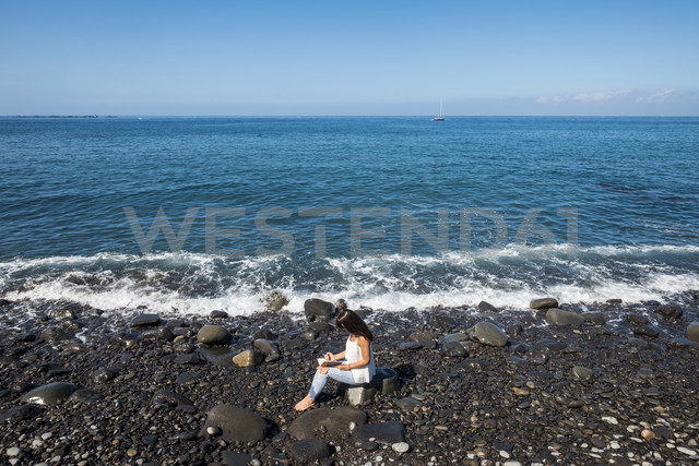 Woman with notebook sitting on stony beach at seafront - SIPF000423