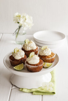 Four lime cup cakes with cream cheese topping on cake stand - EVGF002944
